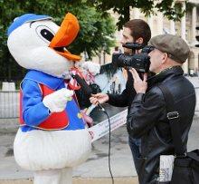 Photo : Interview d'un militant déguisé en canard à foie gras par deux journalistes