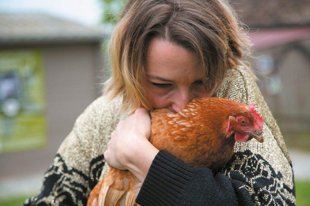 Femme câlinant une poule